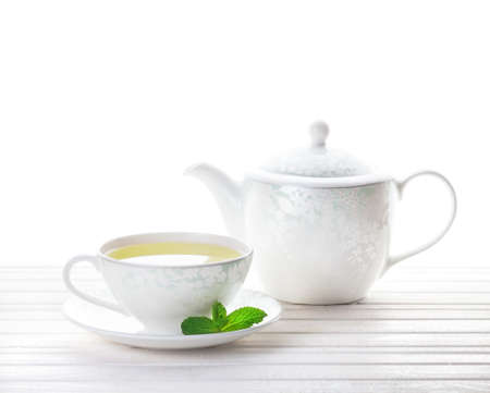 Photo for Mint tea in the cup near teapot at white background - Royalty Free Image