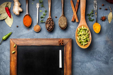 Photo for Various Spices like turmeric, cardamom, chili, ginger, star anise and cinnamon near blackboard on grunge background. Free space for your text - Royalty Free Image