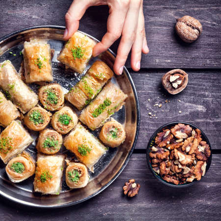 Photo for Hand holding Turkish baklava near walnuts on wooden background - Royalty Free Image