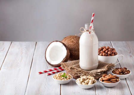 Foto de Vegan milk from nuts in the bottle with red stripped straw around various nuts on white wooden table - Imagen libre de derechos