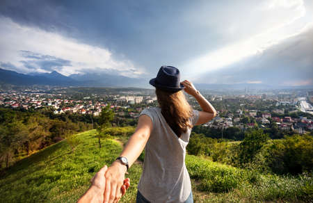 Photo for Woman in gray t-shirt and hat holding man by hand and looking to the city view in the mountains at dramatic sky  - Royalty Free Image