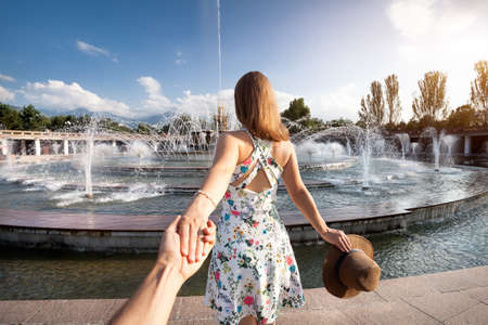 Photo pour Woman in white dress with hat holding man by hand and going to fountain in the park in Almaty, Kazakhstan - image libre de droit