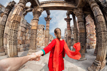 Photo pour Woman in red costume with scarf leading man by hand to Qutub Minar tower in Delhi, India - image libre de droit