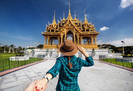 Photo pour Woman in hat and green checked shirt leading man to the Ananta Samakhom Throne Hall in Thai Royal Dusit Palace, Bangkok, Thailand - image libre de droit