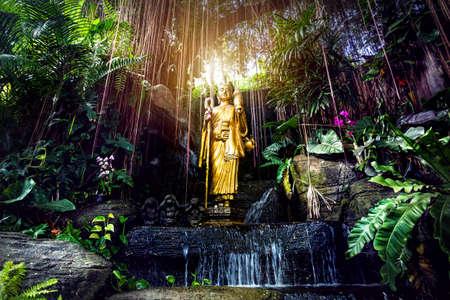 Foto de Golden Buddha statue in the tropical garden with waterfall in Wat Saket Golden Mountain Temple in Bangkok - Imagen libre de derechos
