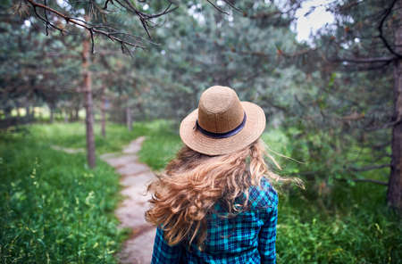Photo pour Young woman in brown hat and green checked shirt with long hair flow in the wind under pine tree in the forest  - image libre de droit