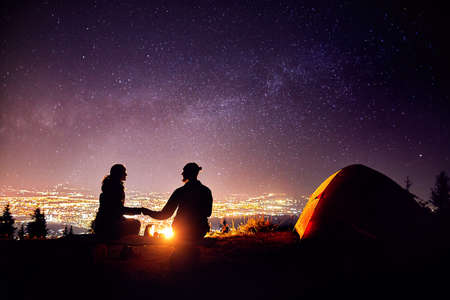 Photo pour Happy couple in silhouette sitting near campfire and orange tent. Night sky with milky way stars and city lights at background. - image libre de droit