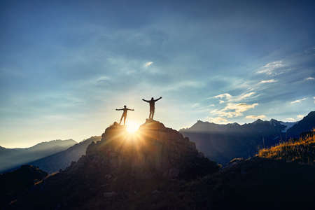 Photo pour Two Hikers in silhouette stands on the rock in the beautiful mountains with rising hands at sunrise sky background - image libre de droit