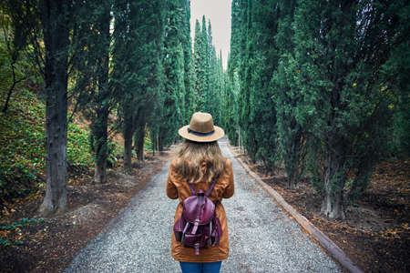 Photo for Woman in brown hat with backpack looking at cypress alley in botanical garden of Tbilisi, Georgia - Royalty Free Image