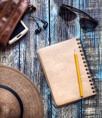 Photo for Vintage Paper journal with empty space for your text near travel hat, sunglasses and bag with smartphone on wooden table - Royalty Free Image