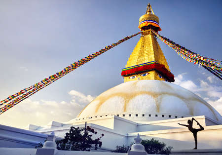 Photo pour Silhouette of man doing yoga natarajasana at Bodnath Great Buddhist Stupa with prayer flags in Kathmandu - image libre de droit