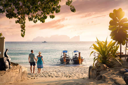 Photo pour Happy couple on the tropical beach of Phi Phi island at sunset in Southern Thailand. Travel magazine concept. - image libre de droit