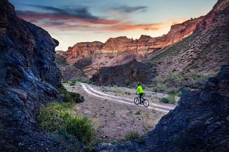 Photo pour Rider in green jacket at mountain bike in the desert Charyn Canyon at sunrise in Kazakhstan. Extreme Sport Concept. - image libre de droit