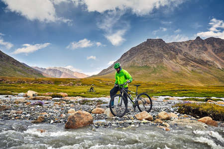 Photo pour Man with mountain bike crossing the river in the wild mountains against cloudy sky background. - image libre de droit