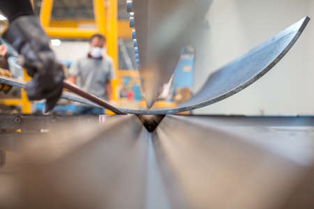 Foto de Asian worker in factory at metal workshop - bender - Imagen libre de derechos