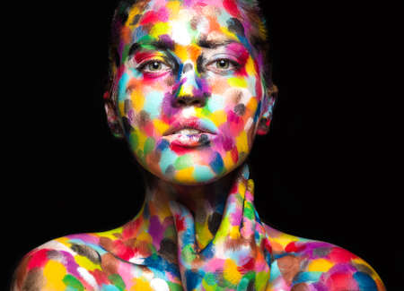 Foto de Girl with colored face painted. Art beauty image. Picture taken in the studio on a black background. - Imagen libre de derechos