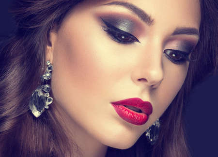 Foto de Beautiful woman with arabic make-up, red lips and curls. Beauty face. Picture taken in the studio on a gray background. - Imagen libre de derechos