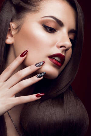 Foto de Pretty girl with unusual hairstyle, bright makeup, red lips and manicure design. Beauty face. Art nails. Picture taken in the studio on a red background. - Imagen libre de derechos