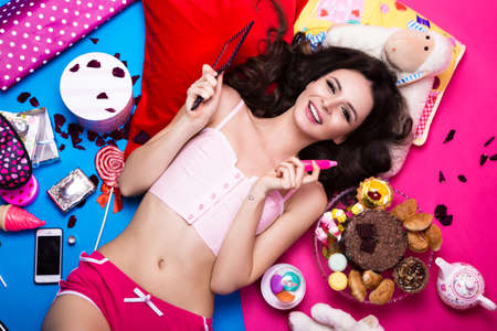 Photo pour Beautiful fresh girl doll lying on bright backgrounds surrounded by sweets, cosmetics and gifts. Fashion beauty style. Photos shot in the studio. - image libre de droit
