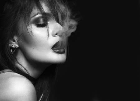 Foto de Beautiful sexy brunette girl with bright makeup, red lips, smoking with smoke from mouth. beauty face. Black and white. Photos shot in the studio on a black background. - Imagen libre de derechos