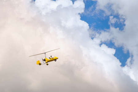 Foto de Small helicopter for two person flying on the cloudy sky - Imagen libre de derechos