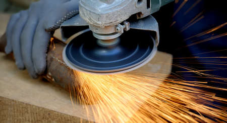 Photo pour Worker cutting metal with grinder. Sparks while grinding iron - image libre de droit