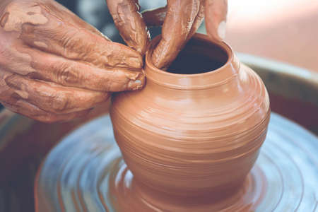 Foto per Hands of a potter. Potter making ceramic pot on the pottery wheel - Immagine Royalty Free