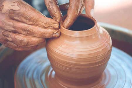 Photo pour Hands of a potter. Potter making ceramic pot on the pottery wheel - image libre de droit