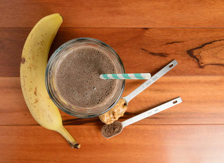 Photo for Chocolate banana smoothie in a glass on a wooden table. - Royalty Free Image