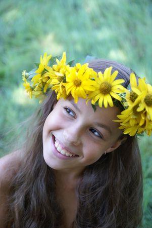 Cheerful preteen girl in yellow flower garland on green grass background