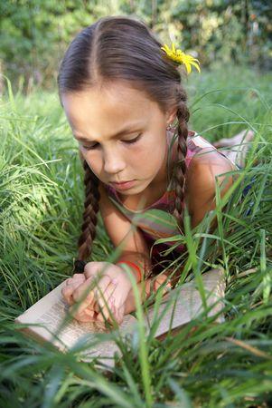 Preteen girl reading book on green grass background