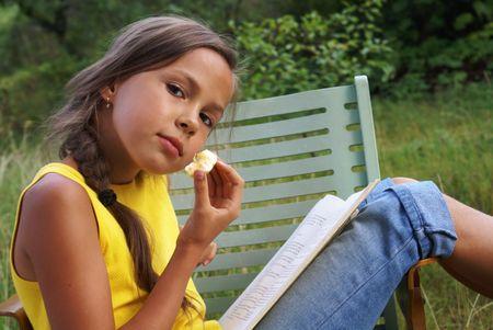 Reading preteen girl on green grass background