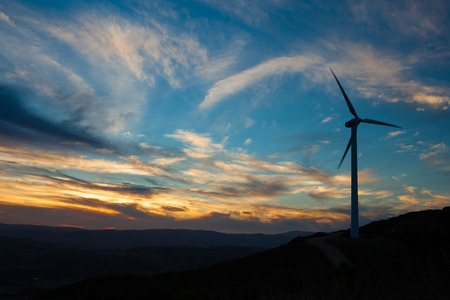 Photo for A soiltary wind turbine silouhetted against a sunsetting blue and orange sky - Royalty Free Image