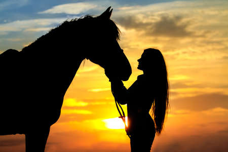 Foto de Girl with horse silhouette against sunset sky - Imagen libre de derechos