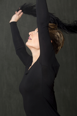Photo for Attractive young woman dancer with short hair, in a scoop neck black dress, throwing a fuzzy black boa over her head in the studio. - Royalty Free Image