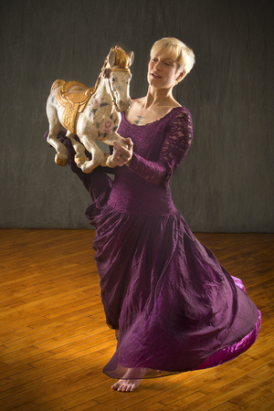 Photo for Young woman in flowing, vintage purple dress, dancing with an antique carousel horse in the studio. - Royalty Free Image