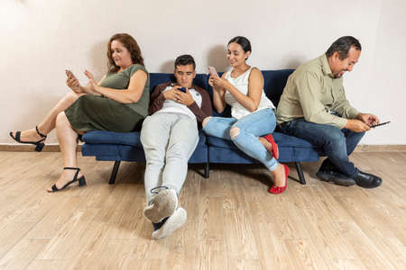 Foto de True Latin family, dad, mom, son and daughter sitting on blue sofa each interacting with their own cell phone. - Imagen libre de derechos