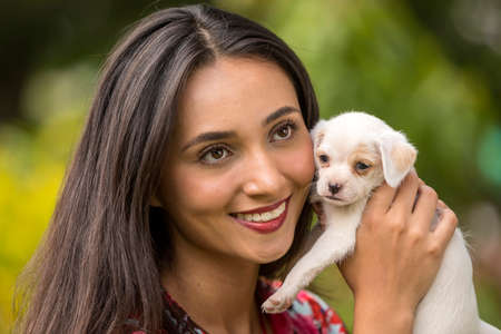 Foto de Beautiful young latin woman in the park with a small white puppy in her hands. - Imagen libre de derechos