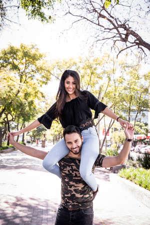 Foto de Young couple man and woman in love, having fun and kissing in the public park. - Imagen libre de derechos