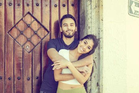 Foto de Couple in love outside a rustic house with wooden door. - Imagen libre de derechos