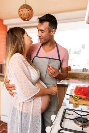 Foto de Young real couple of happy married in the kitchen of their house. Pregnant woman. Husband with apron working - Imagen libre de derechos
