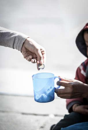 Foto de Detail of woman's hand giving a coin to a homeless person, and sad boy in the background. - Imagen libre de derechos