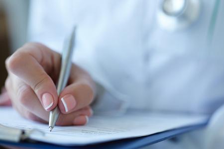 Photo pour Close-up view of female doctor's hands filling patient registration or prescription form. Healthcare, medical and pharmacy concept. - image libre de droit