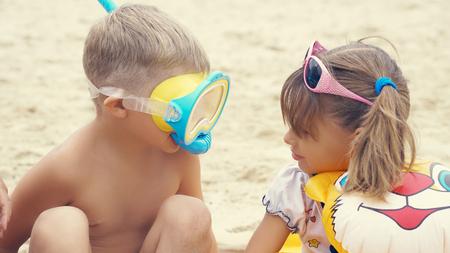 Foto de Portrait of the happy children with swimming mask on head playing onthe sea beach. - Imagen libre de derechos