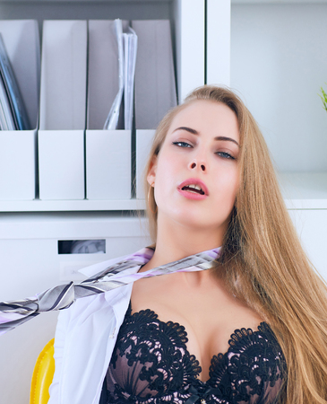 Photo for Sexy secretary undresses in office and pull the tie on her neck. Flirt and desire, office provocation. - Royalty Free Image
