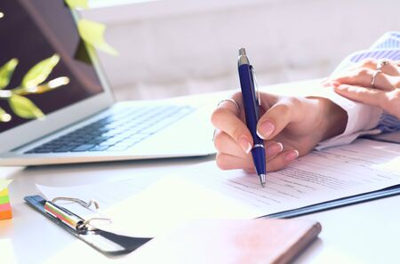 Photo pour Businesswoman sitting at office desk signing a contract or making notes. - image libre de droit