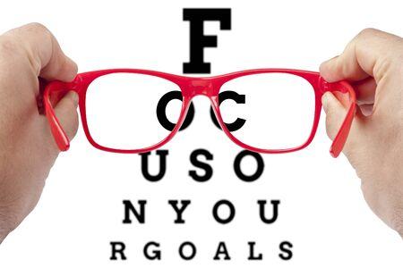 Photo pour Red spectacles focusing on text focus on your goals arranged as eye chart test - image libre de droit