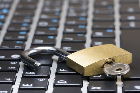 Photo pour Computer security concept with an open padlock with key on the keyboard - image libre de droit