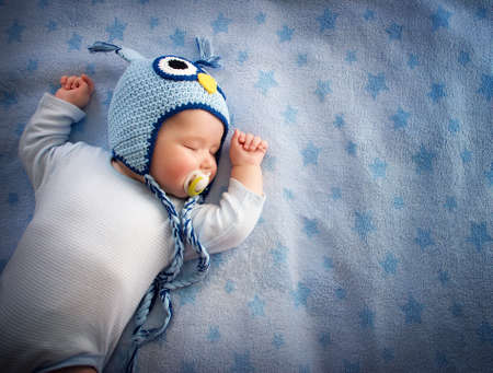 Foto de 4 month old baby in owl hat sleeping on blue blanket - Imagen libre de derechos