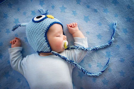 Foto de 4 month old baby in owl sleeping on blue blanket - Imagen libre de derechos